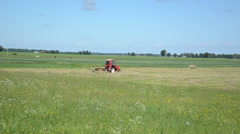 Red tractor ted hay drying grass in agriculture field Stock Footage