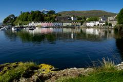 a line of port houses forms the backdrop to the waterfront of portree harbour - stock photo