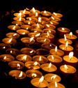 Stock Photo of wax candles lit by the faithful during the celebration of the eucharist