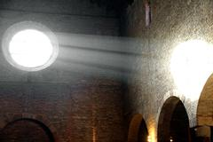 Sunlight that enters from the ancient christian church rose window Stock Photos