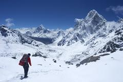 Sherpa guide walking over cho la pass with ama dablam on left and arakam tse  Stock Photos