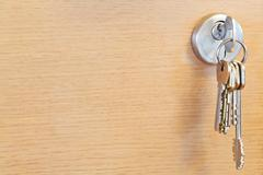 bunch of home keys in lock of wooden door - stock photo