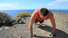 Young man making push-ups outdoors. Sunny day, dolly shot. - stock footage
