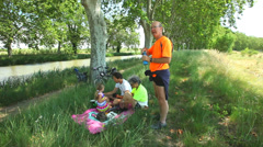 Grand parents enjoying picnic on summer holidays with grand daughter Stock Footage