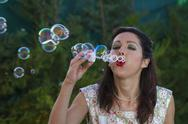 Stock Photo of a beautiful woman blowing bubbles. spring season, rural scene