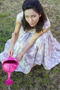 woman watering green garden. mature girl gardening in her backyard. spring se - stock photo