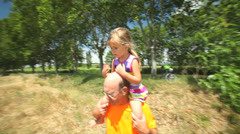 Grandfather carrying grand daughter on shoulders in nature in summer Stock Footage