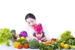 asian mother teach daughter cook - isolated - stock photo