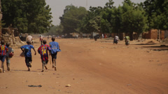 Africa - Boys in football shirts running on dirt road Stock Footage