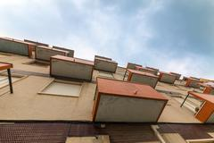 balconies old apartments on cloud sky background - stock photo