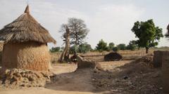 Africa - Mud hut village pan Stock Footage