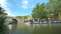 Barges passing bridge in Le Somail on the Canal du Midi, France. Stock Footage