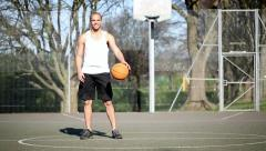 Smiling basketball player bouncing the ball with skill Stock Footage