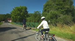 Retired couple cycling on road in village in France Stock Footage