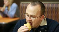 man eating a hamburger at diner - stock footage