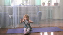 A little girl plays the fool, doing exercises, yoga Stock Footage