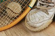 Stock Photo of old tennis ball and sneakers on a wooden floor