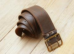 Leather belt with a buckle on a wooden board Stock Photos