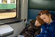Stock Photo of two boys sleeping in a train during their travel