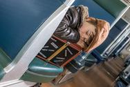 Stock Photo of kid fell asleep on his suitcase in a train
