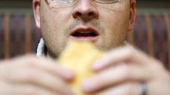 a man eating a hamburger - stock footage