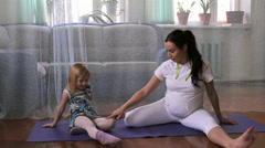 A little girl and a pregnant woman, play, play tricks, do exercises, yoga Stock Footage
