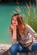 Bored young woman sitting on a lake Stock Photos
