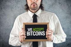 Businessman holding board with title we accept bitcoins Stock Photos
