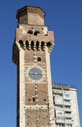 contrast between the ancient bell tower of the church and the modern skyscrap - stock photo