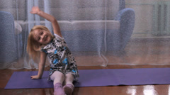 A little girl plays the fool, doing exercises, yoga, play with a ball Stock Footage