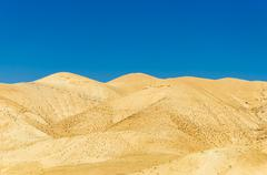 Gold sand dunes in desert with blue sky Stock Photos