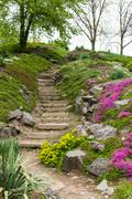 Stone stairs in the park surrounded by flowers Stock Photos