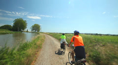 Man cycling on dirt track near river in France Stock Footage