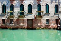 fassade of old venetian house standing in water - stock photo