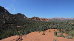 Pan of desert in Sedona, showing green trees and red mountains in the background Stock Footage