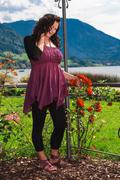 Romantic woman with oversize in a rose garden on the lake - stock photo