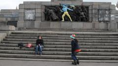 Teenagers playing skaters in front of a monument painted in colors of Ukraine Stock Footage