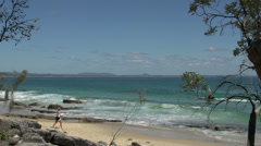 Girl walking at the beach with jet sky passing by in Noosa National Park Stock Footage