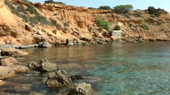 Europe Spain Balearic Ibiza coves and landscapes 049 a red rockface Stock Footage