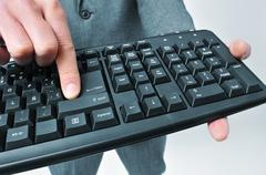 Stock Photo of man in suit pressing the enter key of a keyboard