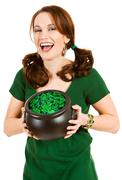 Stock Photo of green: excited woman holding pot of holiday coins and beads