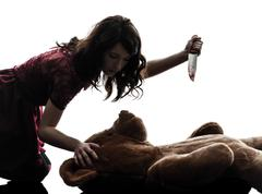 Strange young woman killing her teddy bear silhouette Stock Photos