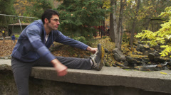 Young Guy Stretches Before Run in Park Stock Footage