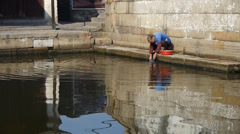 Chinese old woman wash cloths under bridge,china water town life. Stock Footage