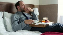 Young businessman eating tasty breakfast in hotel bed HD Stock Footage