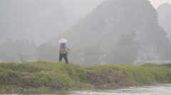 VIETNAMESE WOMAN WALKING ALONG RIVER Stock Footage