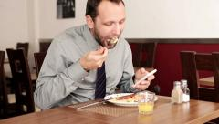 Businessman texting on smartphone and eating tasty english breakfast HD Stock Footage