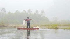 VIETNAMESE FISHERMAN IN LONG BOAT - stock footage
