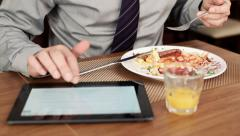 Businessman using tablet and eating tasty english breakfast HD Stock Footage