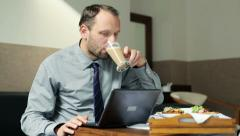 Businessman working on laptop, drinking coffee in hotel room HD Stock Footage